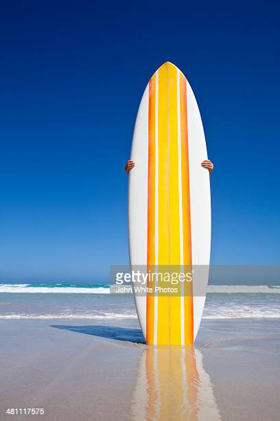 Striped retro surfboard on a beach. Australia