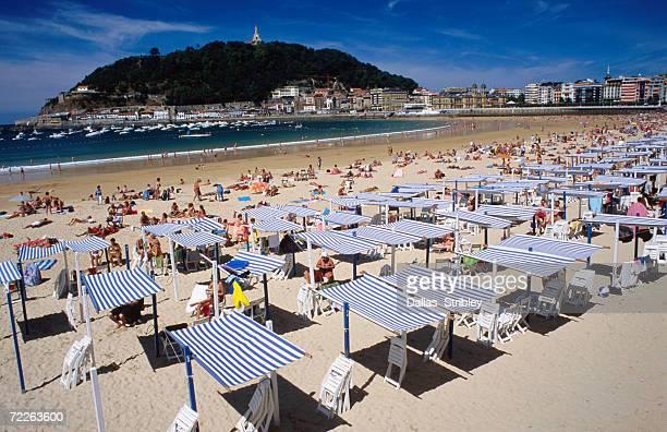 Striped sunshades at Playa de la Concha with Mt Urgull in background, San Sebastian, Spain