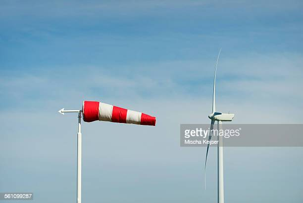 Striped wind sock and wind turbine against blue sky, Netherlands