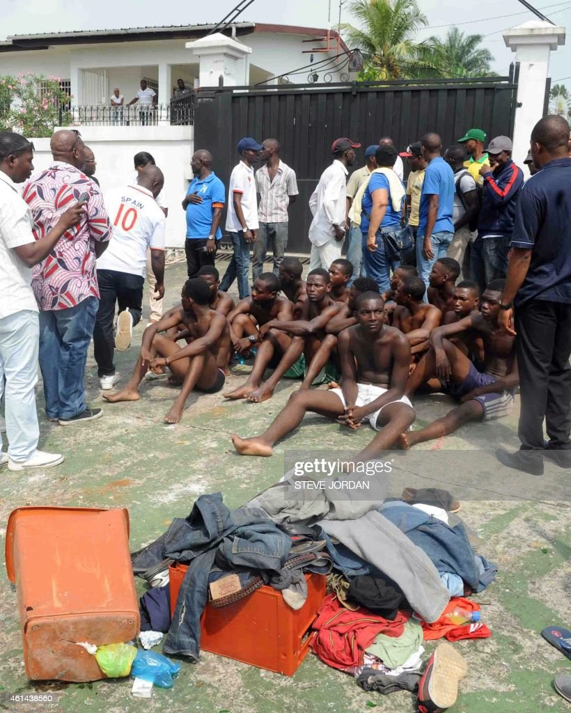 Stripped down to their underwear a group of men sitting on the ground outside the residence of former Africa Union commission president Jean Ping...