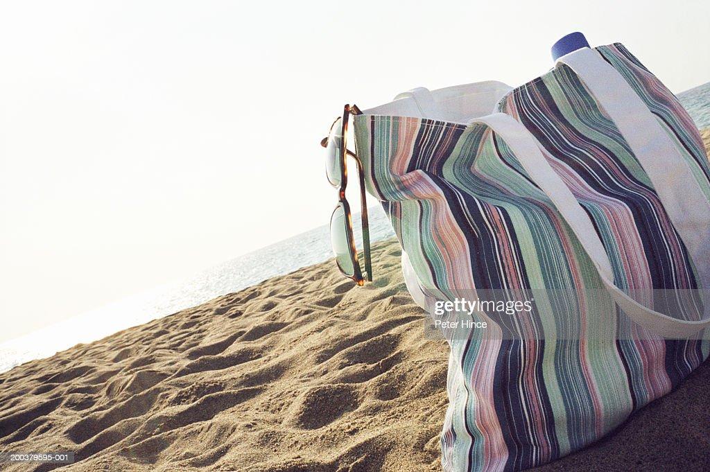 Stripy bag with sunglasses on beach, ground view : Stock Photo