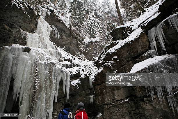 Strollers stand in front of a frozen waterfall at the Breitachklamm gorges on January 8 2010 in Oberstdorf Germany Up to 40cm of new snow is...