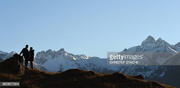 Strollers stand in front of an Alps panorama prior to the ski jumping event in Oberstdorf southern Germany which is the first station of the...