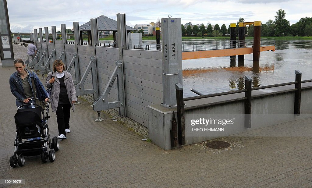 Strollers walk past a wall erected against the floods of the Oder river on May 24, 2010 in Frankfurt/Oder near the Polish German border. Public authorities expect the highest level of the flood wave to come to Germany on Wednesday or Thursday. The death toll from flooding in Poland rose to 15 Monday as torrential rain swelled major rivers to levels unseen in more than a century and rescuers from across Europe battled to prevent further tragedy.