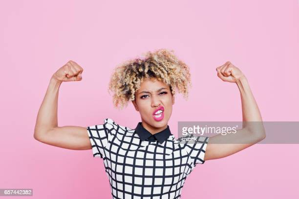 Strong afro american young woman flexing muscles