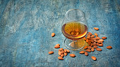 Strong alcoholic beverage amaretto liqueur in sniffer glass for tasting on blue concrete background with copy space