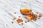 Strong alcoholic beverage amaretto liqueur in sniffer glass for tasting on white wooden background with copy space