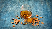 Strong alcoholic beverage amaretto liqueur in sniffer glass for tasting on blue concrete background