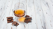 Strong alcoholic beverage cognac in sniffer glass with chocolate bar for tasting on white wooden background with copy space