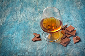 Strong alcoholic beverage cognac in sniffer glass with chocolate bar for tasting on blue concrete background with copy space
