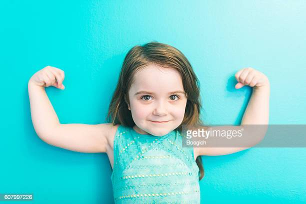 Strong American Girl Looking at Camera Shows Muscles Raising Arms