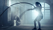 Strong Athletic Woman Exercises with Battle Ropes as Part of Her Cross Fitness Gym Workout Routine. She's Covered in Sweat and Training Takes Place in a Abandoned Factory Remodeled into Gym.