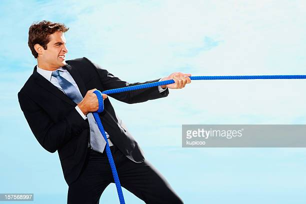 Strong business man pulling a success rope towards his side