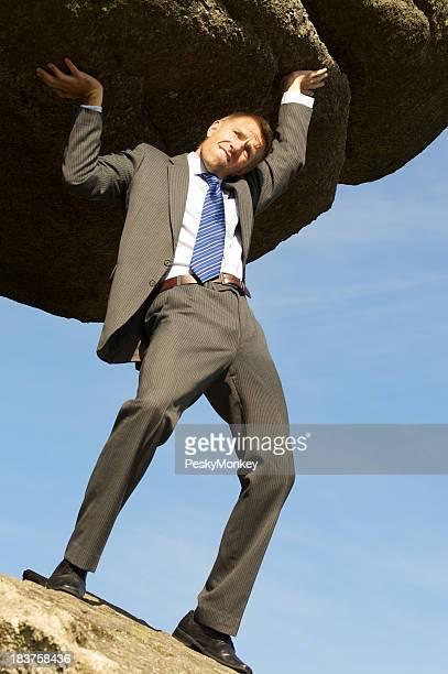 Strong Homme d'affaires tenant un énorme rocher Boulder dans le ciel