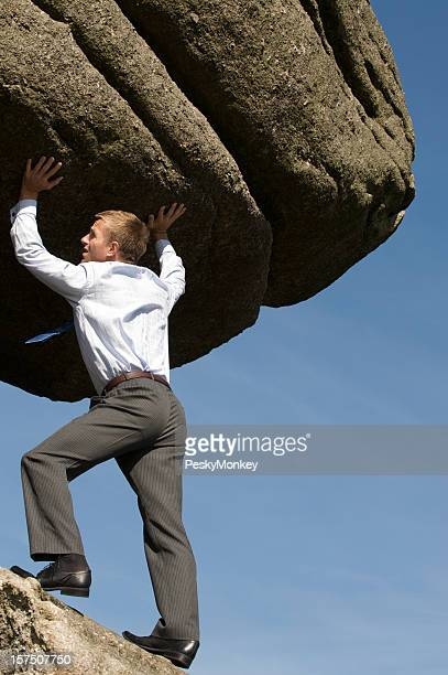 Strong Businessman Lifting Massive Boulder Outdoors in Blue Sky