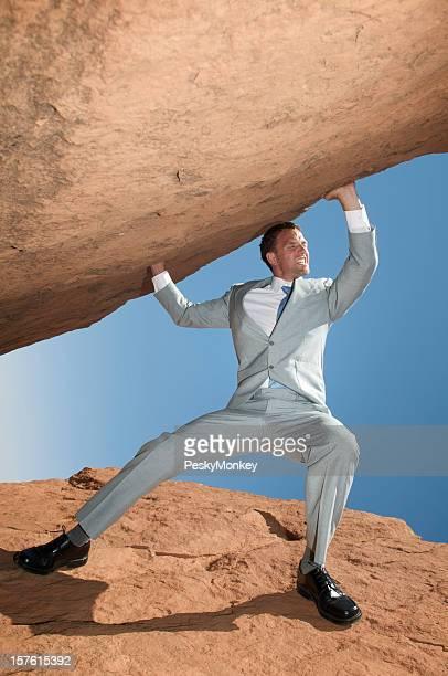 Strong Businessman Struggling Lifting Massive Boulder