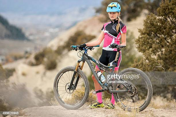 Strong female bike racer posing with her bike.