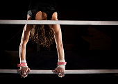 Lighting highlighs the muscles and graceful lines of this female gymnast doing a handstand atop the lower of two uneven bars.