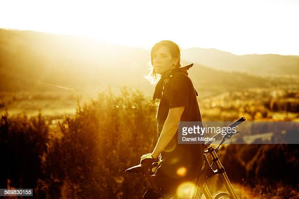 Strong female sitting on her bike during sunset.