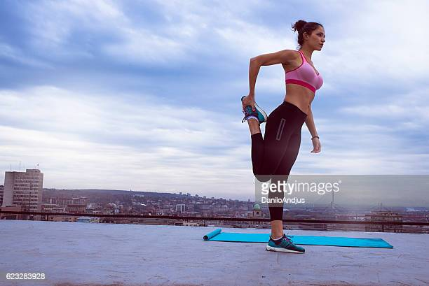 strong fit woman stretching on the rooftop before working out