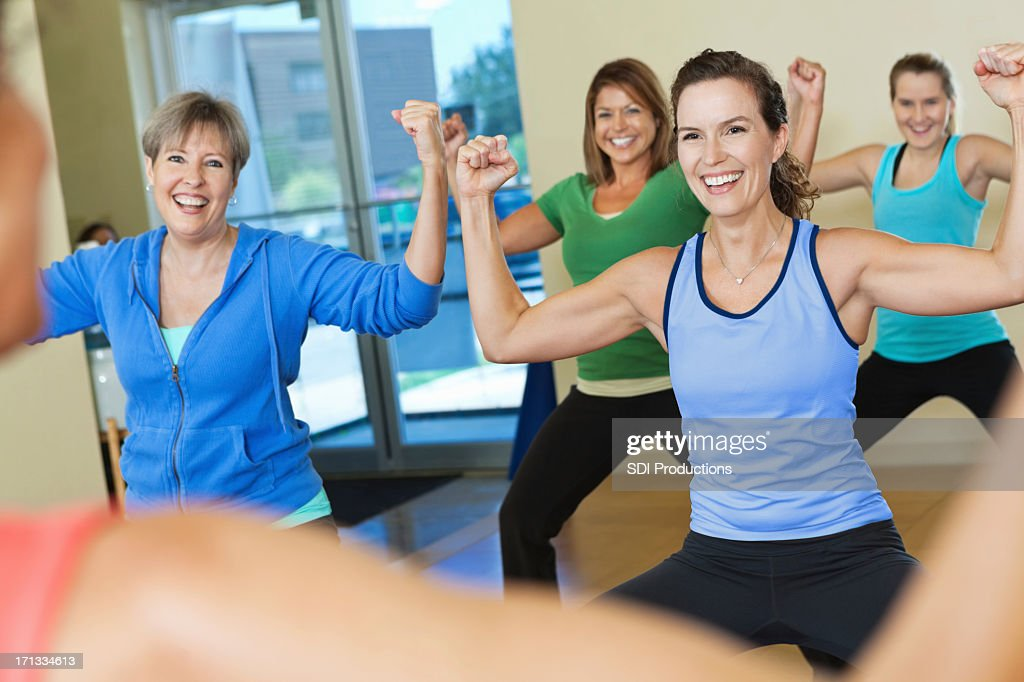 Strong group of women exercising together in fitness class : Stock Photo
