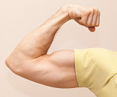 Strong male arm shows biceps. Close-up photo