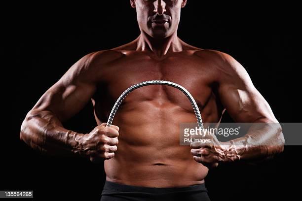 Strong man bending steel bar