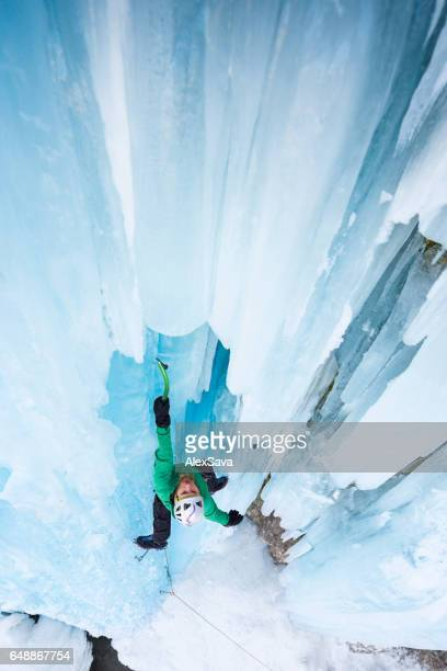 Strong man climbing on blue icicles outdoor