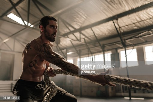 Strong man pulling heavy rope at gym : Stock Photo