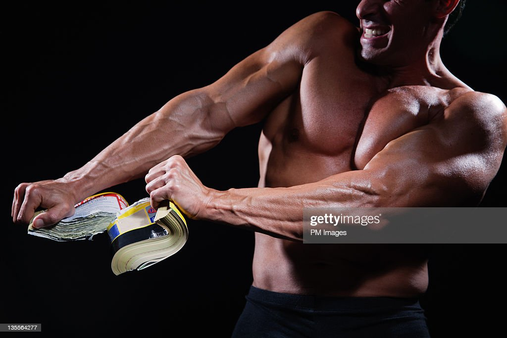 Strong man ripping phone book : Stock Photo