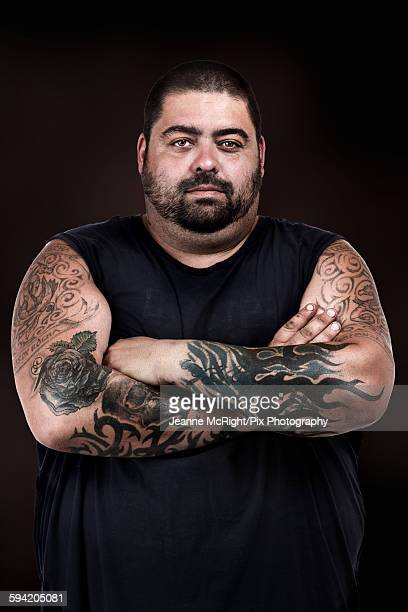 Strong man with tattooed arms crossed
