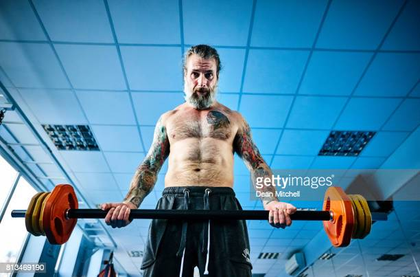 Strong mature guy doing exercises with a barbell in the gym