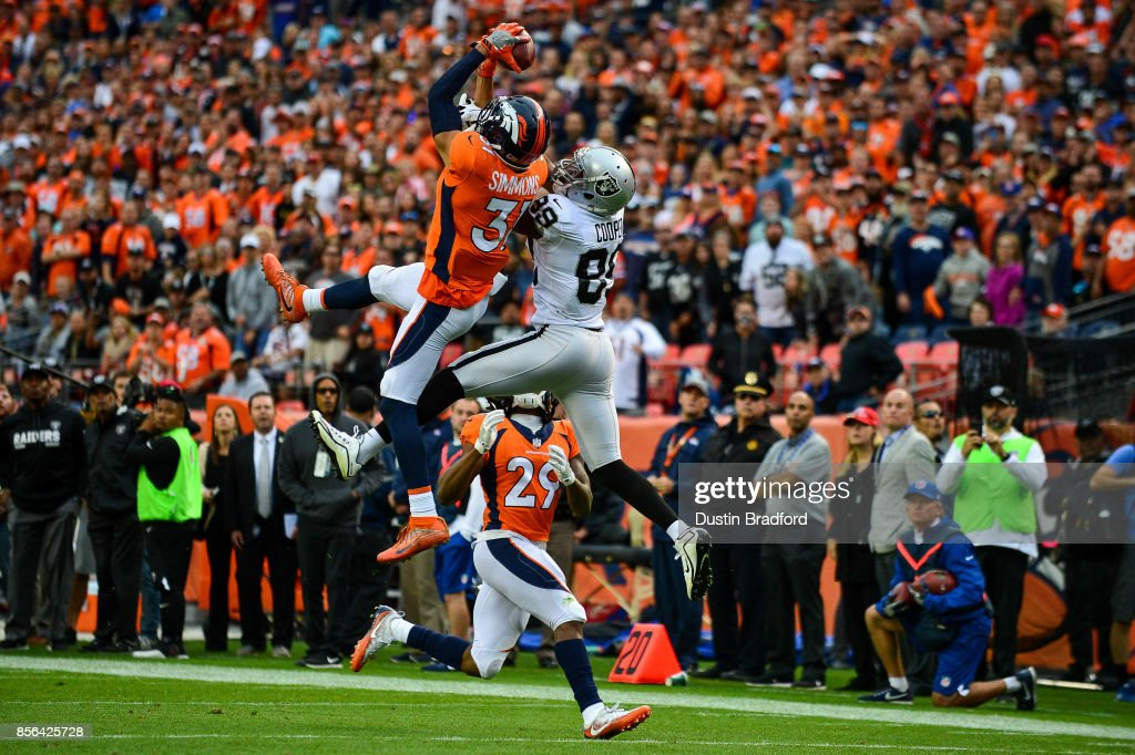 Strong safety Justin Simmons #31 of the Denver Broncos intercepts a deep pass intended for wide receiver Amari Cooper #89 of the Oakland Raiders as free safety Bradley Roby #29 covers the play late in the fourth quarter of a game at Sports Authority Field at Mile High on October 1, 2017 in Denver, Colorado.