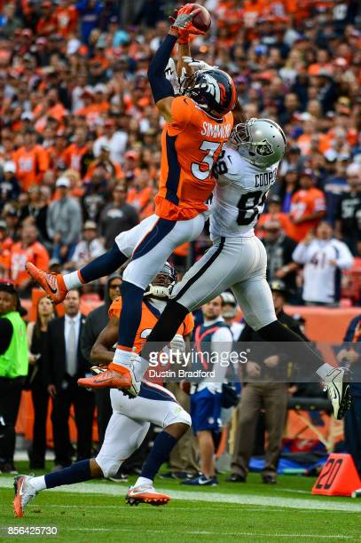 Strong safety Justin Simmons of the Denver Broncos intercepts a deep pass intended for wide receiver Amari Cooper of the Oakland Raiders as free...