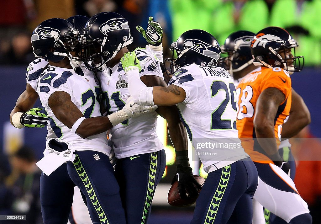 Strong safety Kam Chancellor #31 of the Seattle Seahawks celebrates his interception with teammates against the Denver Broncos in the first quarter during Super Bowl XLVIII at MetLife Stadium on February 2, 2014 in East Rutherford, New Jersey.
