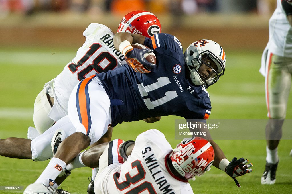 Strong safety Shawn Williams #36 and free safety Bacarri Rambo #18 of the Georgia Bulldogs tackle tight end Brandon Fulse #11 of the Auburn Tigers on November 10, 2012 at Jordan-Hare Stadium in Auburn, Alabama. Georgia leads Auburn 28-0 at halftime.