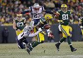 Strong safety Tavon Wilson of the New England Patriots grabs wide receiver Davante Adams of the Green Bay Packers as strong safety Patrick Chung...