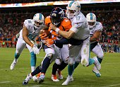 Strong safety TJ Ward of the Denver Broncos is tackled out of bounds by quarterback Ryan Tannehill of the Miami Dolphins after a fourth quarter...