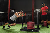 Sled push exercise. Strong muscular sportsman during his cross training workout with his trainer