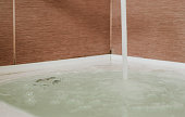 A strong stream of water pours into the tub. Water pours out. Tub overflows.