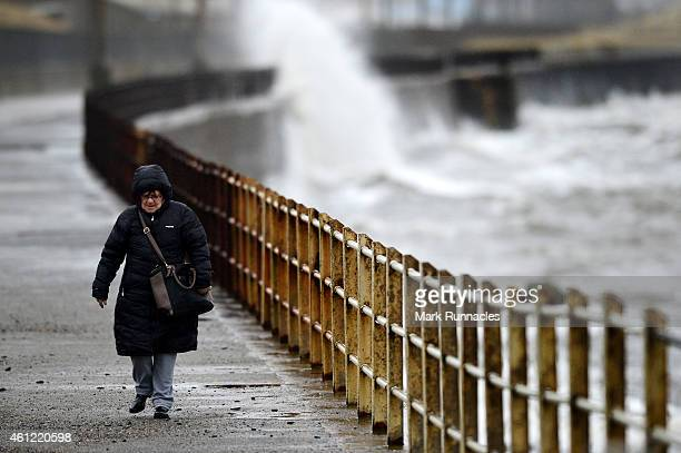 Strong waves begin to build as a woman walks along nest to the sea defences on January 9 2015 in Saltcoats Scotland A vigorous depression over the...