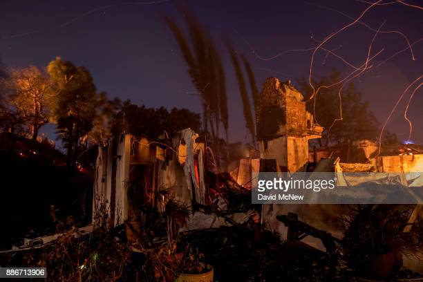 Strong wind blows embers across the smoldering ruins of a house at the Creek Fire on December 5 2017 in Sunland California Strong Santa Ana winds are...