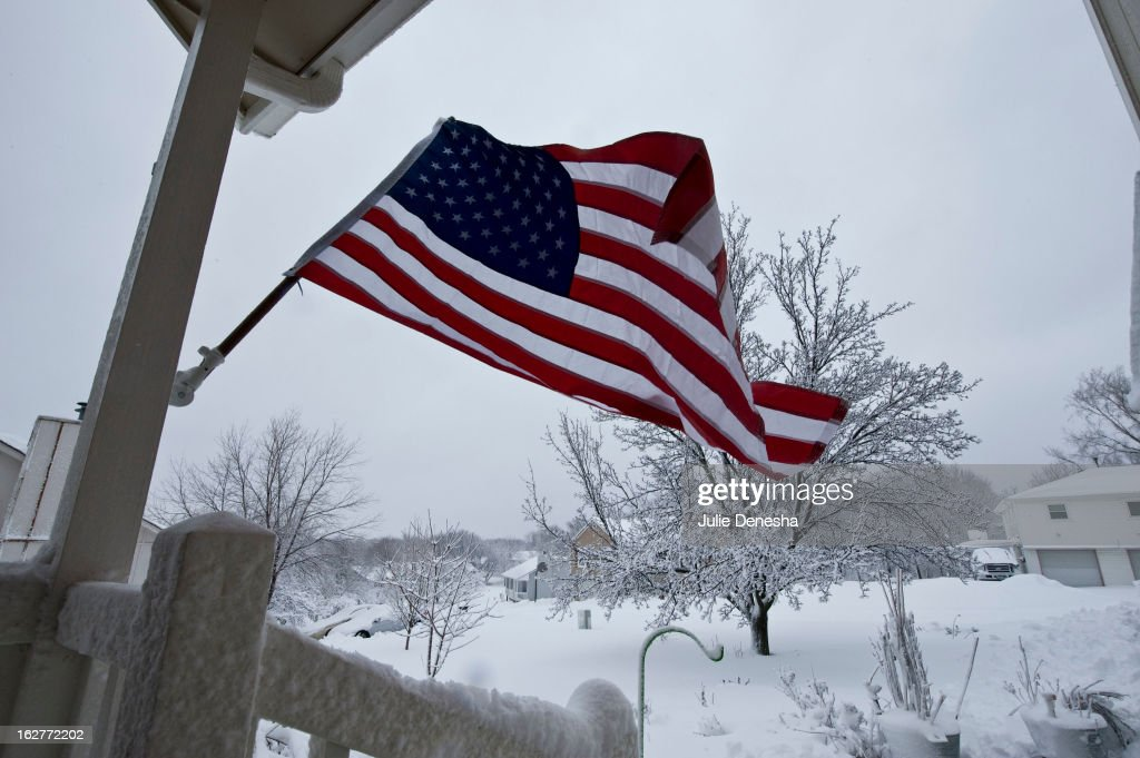 Strong winds and snow whip a flag on the porch of a home after a snowstorm hit the midwest February 26, 2013 in Merriam, Kansas. This is the second major snowstorm the midwest has seen this week dropping a half-foot or more of snow across Missouri and Kansas and cutting power to thousands.