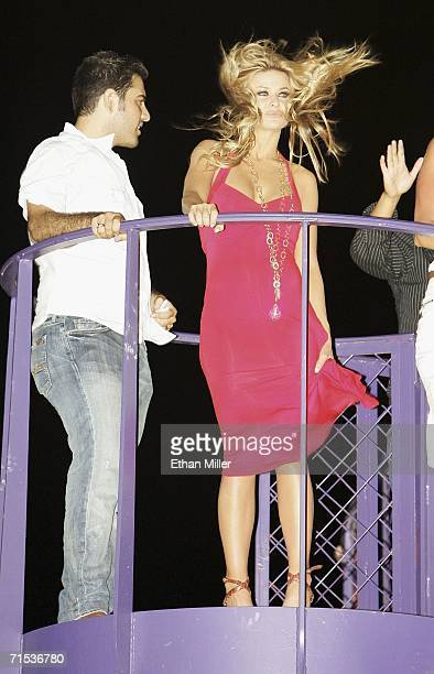 Strong winds whip actress Carmen Electra's hair as she watches a performance by singer Rihanna at the Voodoo Lounge on top of the Rio Hotel Casino at...