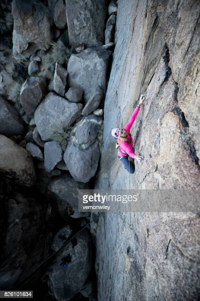Strong woman climbing steep granite in the mountains