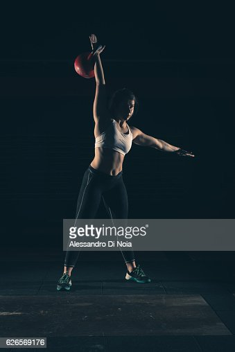 Strong woman lift kettlebell on a gym