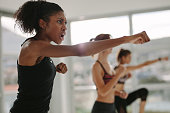 Strong young females exercising in gym. Women doing punching workout in fitness club.