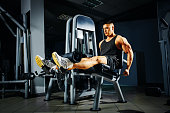 Strong young man doing legs exercise in the gym