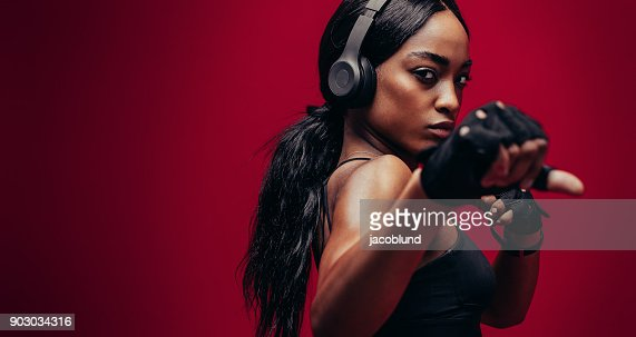 Strong young woman practising boxing : Stock Photo