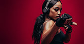 Strong young woman with headphones practising boxing. African female boxer exercising on red background